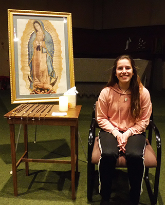 A young lady seated in front of a picture of Our Lady of Guadalupe